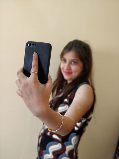 Young woman taking selfie through mobile phone by wall at home