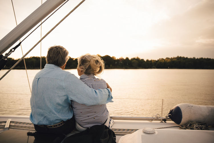 Rear view of couple on boat at sea against sky