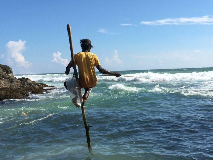 Fisherman on stilt at sea against sky
