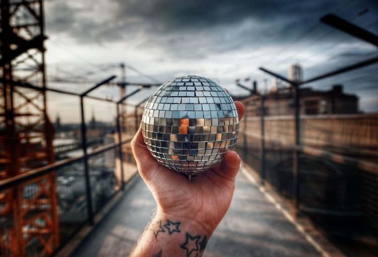 Cropped hand holding disco ball outdoors