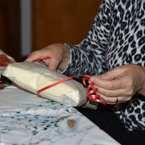 Midsection of woman wrapping gift on table