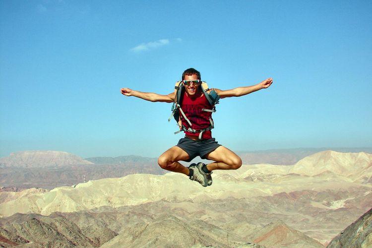 Full length of man jumping over landscape against sky
