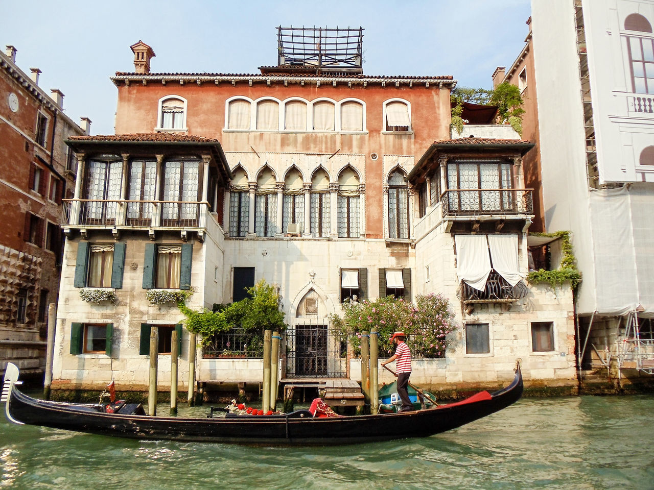building exterior, architecture, nautical vessel, canal, built structure, boat, transportation, day, real people, mode of transport, gondola, water, outdoors, men, waterfront, oar, gondolier, gondola - traditional boat, sitting, tree, sailing, rowing, nature, city, sky, people