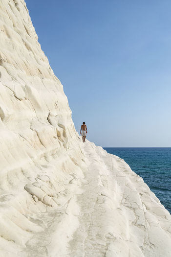 Adventure At The Edge Of Beauty In Nature Blue Clear Sky Day Escapism Exploration Full Length Men Nature Outdoors Remote Rock Formation Rocky Scenics Sea Solitude Tourism Tourist Tranquil Scene Tranquility Vacations