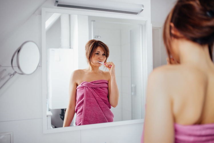 Reflection of woman wrapped in towel while brushing teeth in mirror