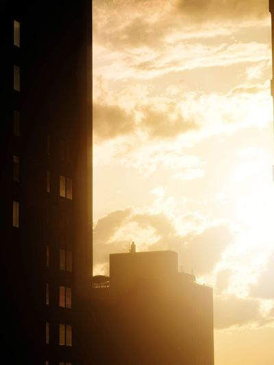 Silhouette buildings in city against sky during sunset