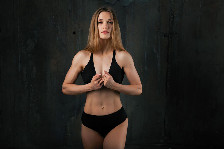 Image of muscular young female athlete wearing black sport wear standing on dark background. Abdominal Muscle Body & Fitness Bodybuilding Adult Beautiful Woman Beauty Clothing Fitness Fitnessmodel Fitnessmotivation Front View Hair Hairstyle Lifestyles Long Hair One Person Real People Sport Wear Sport Woman Sports Clothing Standing Three Quarter Length Women Young Adult Young Women