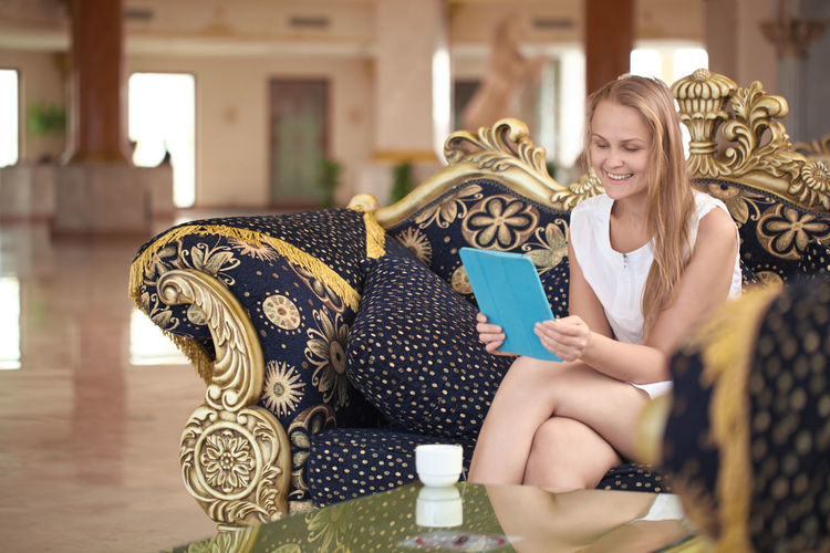 Beautiful happy woman holding digital tablet while sitting on sofa in hotel