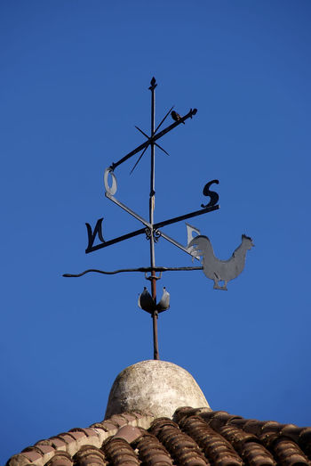 Low angle view of weather vane on roof against clear blue sky