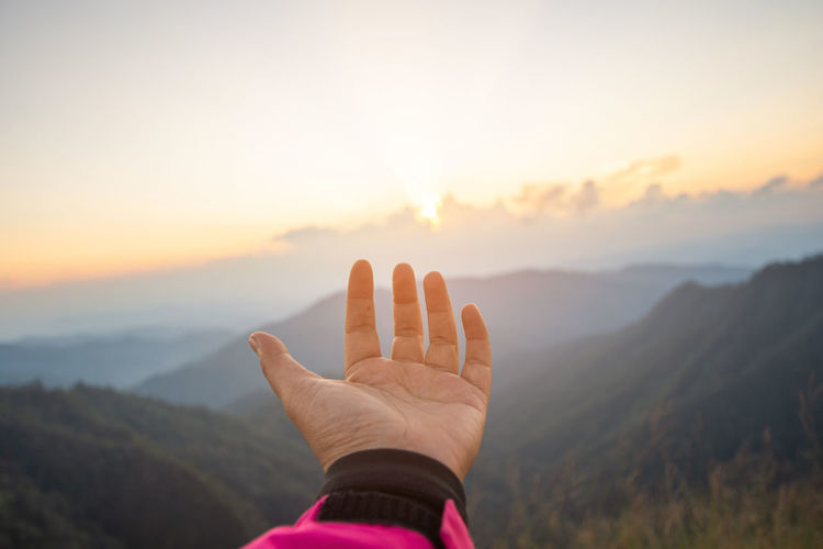 Cropped hand of woman gesturing against mountains and sky