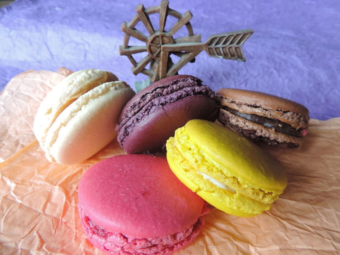 Colorful macaroons and windmill toy on wax paper