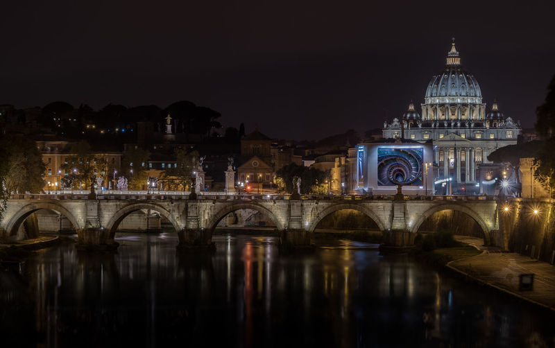 Illuminated st peter basilica by river against clear sky at night