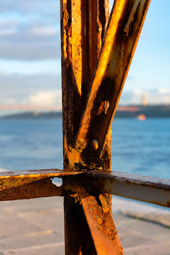 Metal Focus On Foreground Sea Rusty Nature Water Close-up Sky Day No People Outdoors Sunlight Tranquility Rust Decaying Decay And Dereliction Decayed Beauty Orange Color Flaking Seaside Marine Yellow