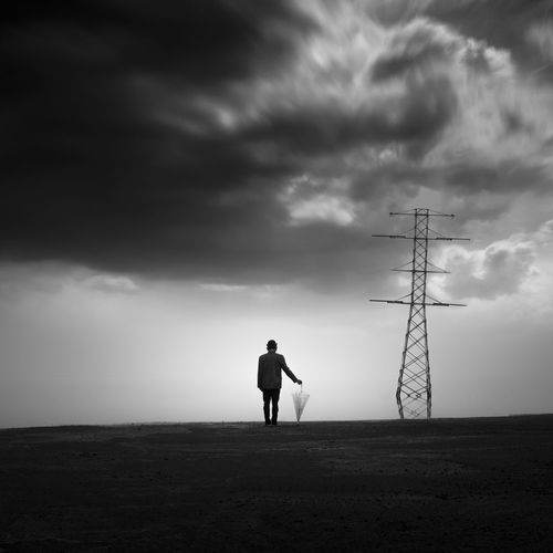 Rear view of silhouette man standing on land against sky at sunset