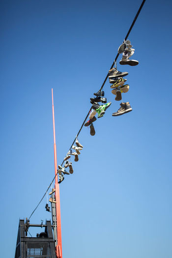 Low Angle View Of Shoes Hanging From Power Cable Against Clear Blue Sky