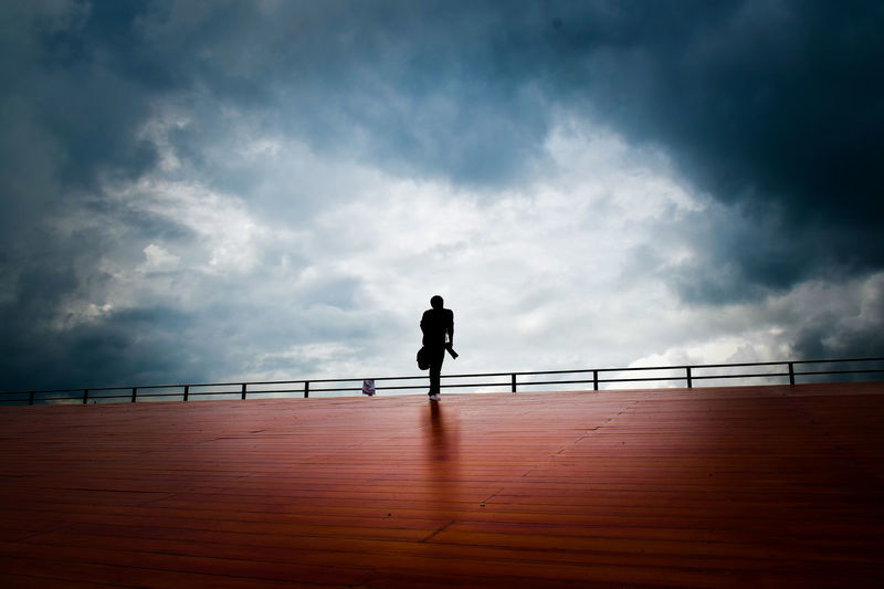 Silhouette man standing by railing against sea