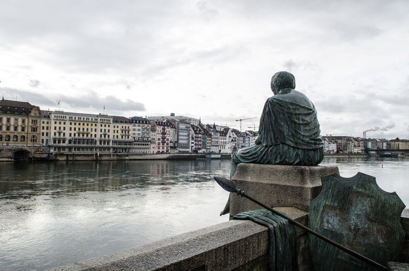 Rear view of statue against river in city