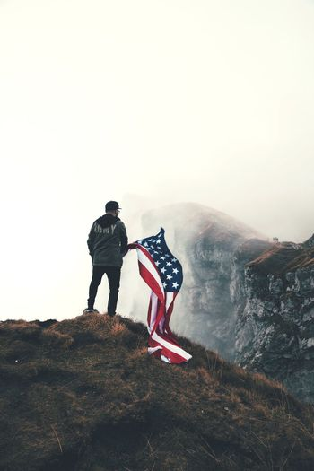 Rear view of man with american flag standing on mountain against sky
