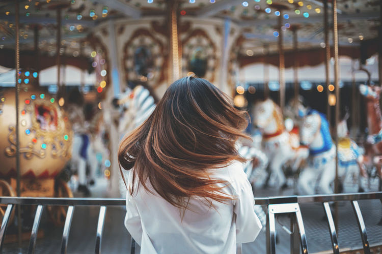 Rear view of woman with tousled hair at amusement park