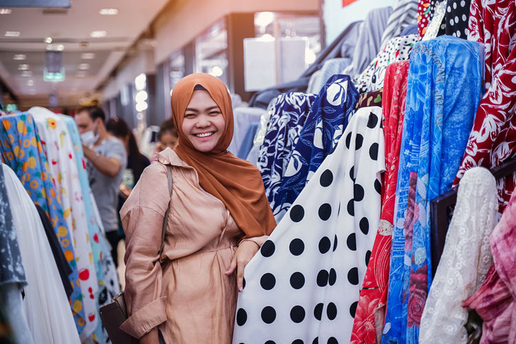 Happy young woman standing at store