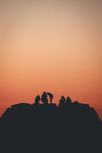 Silhouette people on mountain against orange sky