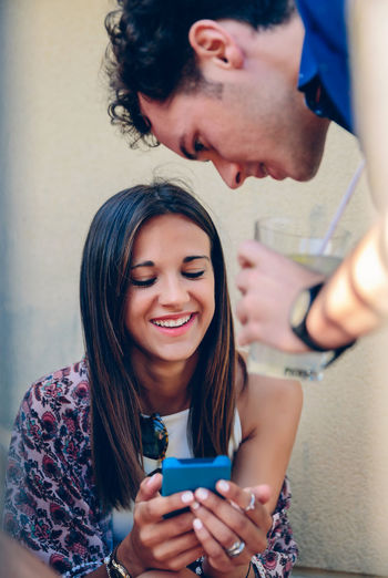Young woman using mobile phone with man against wall