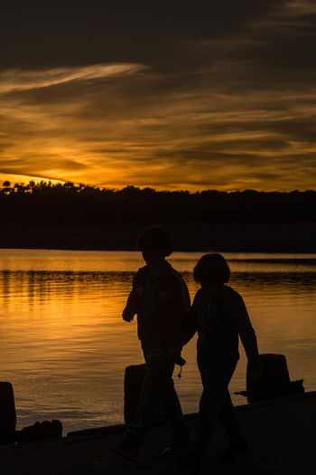 Friends walking on pier against lake during sunset