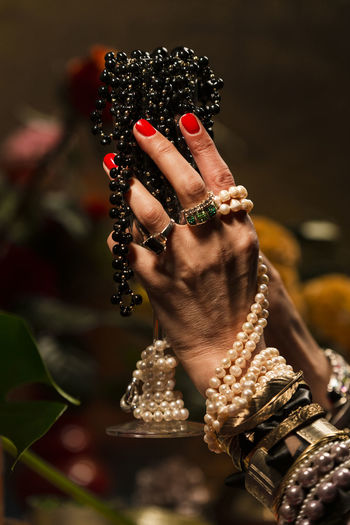 Gestures of a woman with jewelry, pearls, fruits and flowers. Abundance Wealth Celebration Art And Craft Mood Jewelry Gold Pearls Gesture Luxury Human Hand Hand Human Body Part Focus On Foreground One Person Holding Close-up Bracelet Women Real People Body Part Adult Ring Day Bead Human Finger Finger Selective Focus Nail Human Limb Personal Accessory