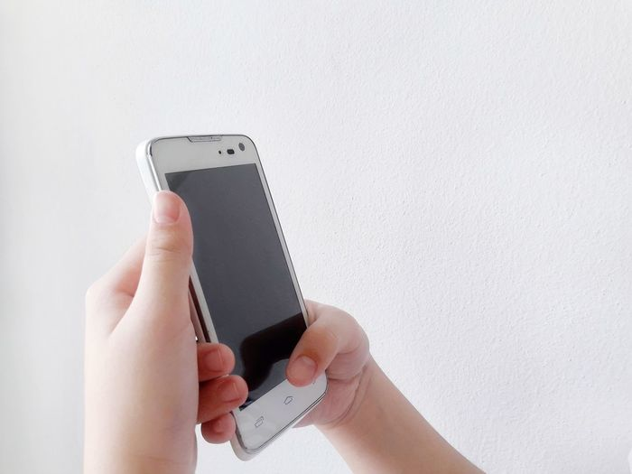 Cropped hands of woman using mobile phone against wall