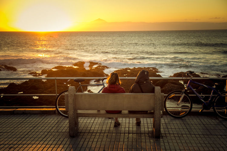 Rear View Of People Sitting On Bench By Sea Against Sky During Sunset