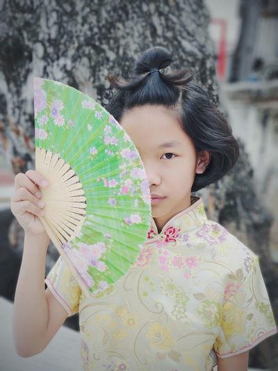Portrait of cute girl holding folding fan standing against tree trunk