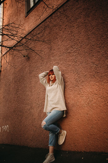 One Person Casual Clothing Full Length Wall - Building Feature Built Structure Standing Clothing Architecture Lifestyles Women Building Exterior Leisure Activity Day Front View Real People Young Adult Adult Hat Outdoors Jeans Human Arm Arms Raised Warm Clothing Hood - Clothing
