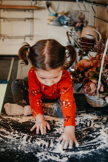 Full length of cute baby girl playing with flour on kitchen counter