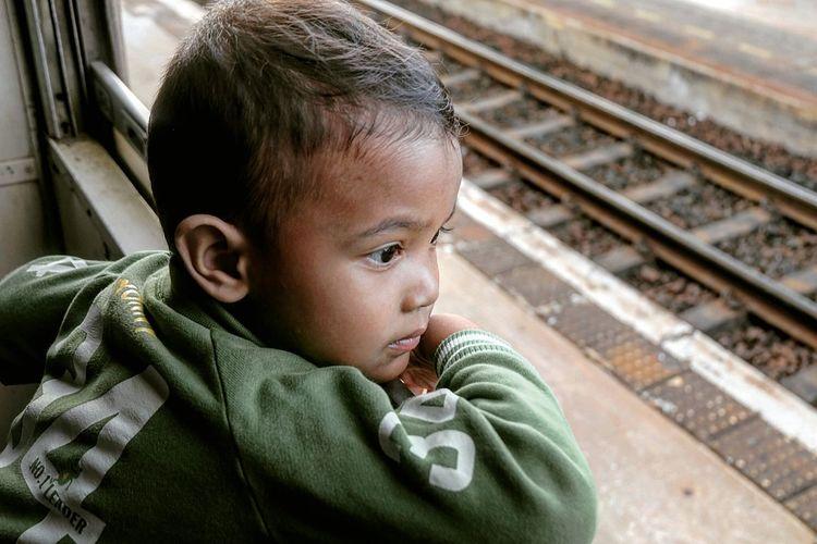 Boy looking through window in train