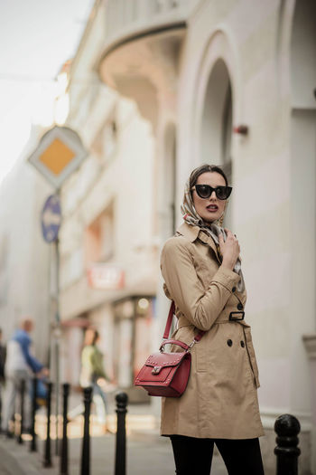 Portrait of fashionable woman in sunglasses standing against building in city