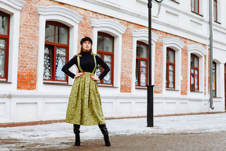 Portrait Of Young Woman Standing On Road Against Building During Winter
