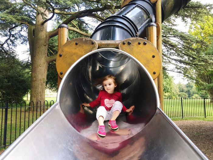 Low angle view of girl on slide at playground