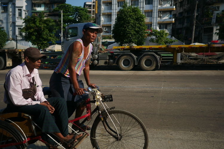 People riding bicycle on street in city