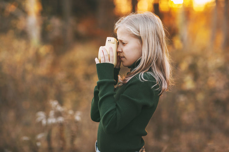 Teenage girl with blond hair takes pictures of nature with a polaroid camera in an autumn park