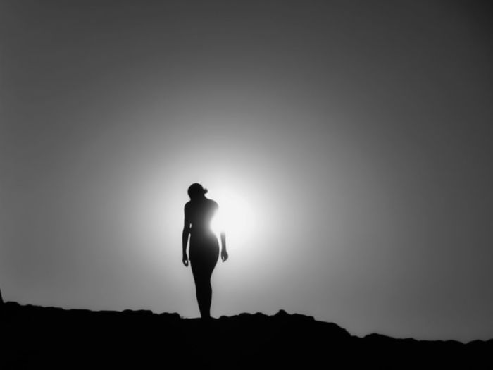 Silhouette man standing against clear sky during sunset