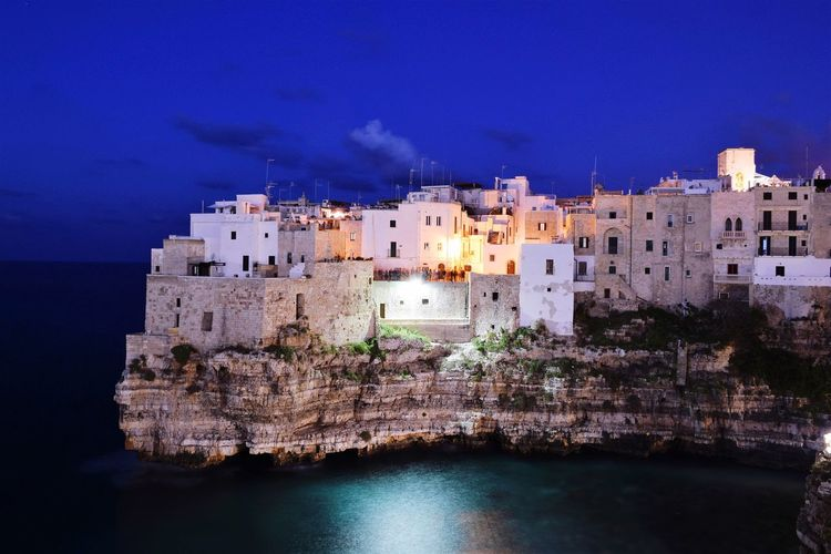Scenic view of rocky coastline and city of polignano, italy at night