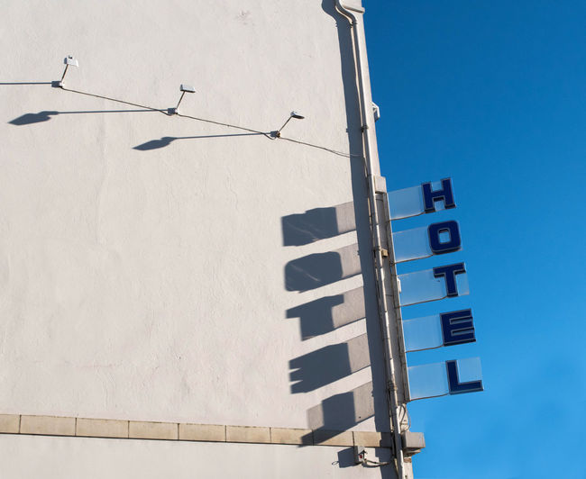 Games of light of a sign of Hotel Architecture Building Exterior Built Structure Clear Sky Communication Day Hotel Low Angle View No People Outdoors Sky Sunset Text