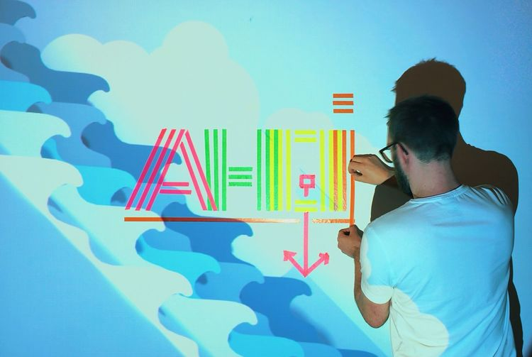 Rear view of man creating text from multi colored papers on wall at home with projection light