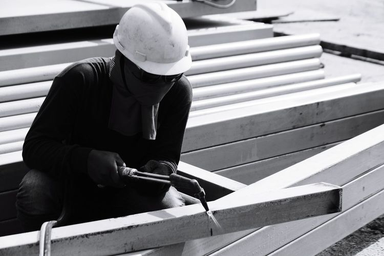 Manual worker welding with tool at construction site
