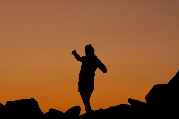 Silhouette woman standing on rock against orange sky