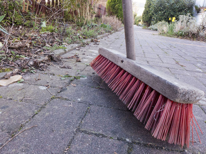 A street broom with rough red long bristles and wooden handle Broom Stick Handle Wooden Red Color Bristles Outdoors No People Day Outside Garden Photography Garden Tools Housekeeping Cleaning Cleaning Equipment Object Broomstick Brush Dirty Footpath Plant Nature Tree Park Paving Stone Park - Man Made Space Front Or Back Yard Architecture Sidewalk