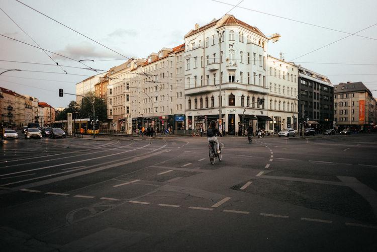 People crossing road against buildings in city
