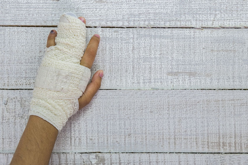 An injured hand Injured Bandage Close-up Day Healthy Lifestyle Human Body Part Human Hand Injury Medication Medications One Person Outdoors People Real People Wood - Material