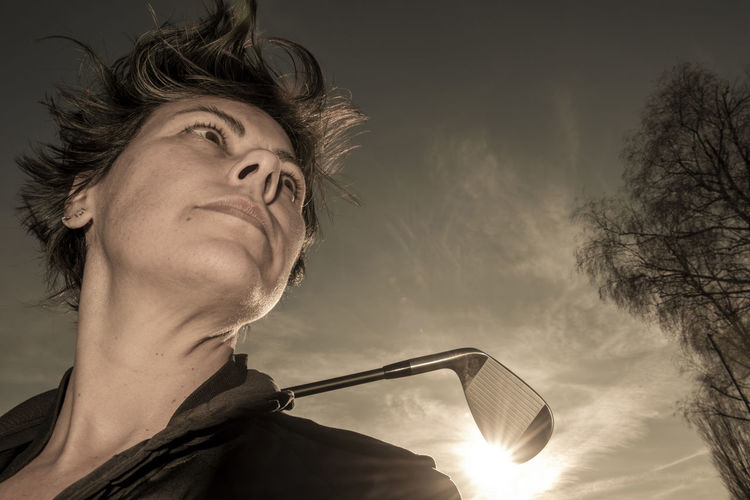 Low angle view of young man looking away against sky