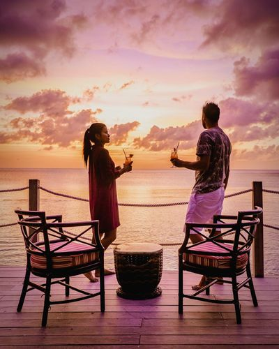 St Lucia Saint Lucia Men Couple Couple - Relationship Cocktails Sunrise Sunset Sunset Silhouettes Beach Boy Colourful Colors Pink Color Orange Color Sunset And Clouds  Friendship Water Sea Full Length Togetherness Sunset Men Beach Sand Relaxation Silhouette Dating Date Night - Romance Romance Dramatic Sky